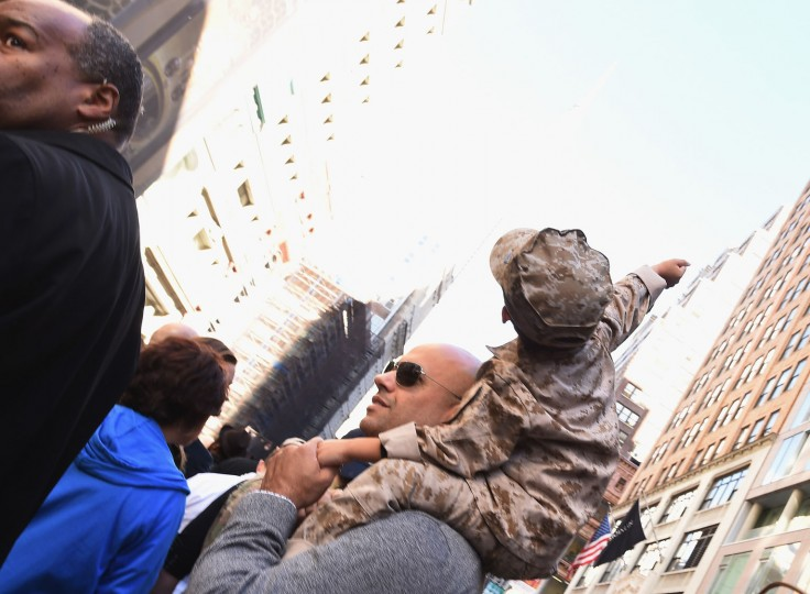 A young boy sits on his Veteran father's shoulders during the annual Veterans Day Parade on November 11, 2016 in New York City. Known as 'America's Parade' it features over 20,000 participants, including veterans of numerous eras, military units, businesses and high school bands and civic and youth groups. (Photo by Michael Loccisano/Getty Images)