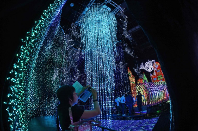 A visitor takes photographs in the Universal Journey during a media preview of Santa's All-Star Christmas at Universal Studios Singapore in Resorts World Sentosa on November 17, 2016. Singapore's Universal Studio broke the Guinness World Record for having the largest indoor display of lightbulbs with 824,961 bulbs in a festive light display separated into eight thematic zones. (ROSLAN RAHMAN/AFP/Getty Images)
