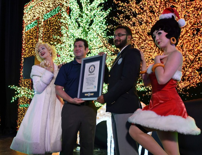 Senior Vice President of Attractions at Resorts World Sentosa Jason Horkin (2nd L) receives a certifcate from Guinness World Record official adjudicator Swapnil Dangarikar (2nd R) while flanked by Marilyn Monroe (L) and Betty Boop (R) impersonators in the Universal Journey during a media preview of Santa's All-Star Christmas at Universal Studios Singapore in Resorts World Sentosa on November 17, 2016. Singapore's Universal Studio broke the Guinness World Record for having the largest indoor display of lightbulbs with 824,961 bulbs in a festive light display separated into eight thematic zones. (ROSLAN RAHMAN/AFP/Getty Images)