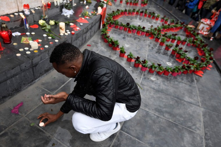 A man puts a candle near a peace symbol made with flowers on place de la Republique in Paris on November 13, 2016 as France marked the first anniversary of the Paris attacks with sombre ceremonies and painful memories for the relatives of the 130 people killed. 130 people were killed on November 13, 2015 by gunmen and suicide bombers from the Islamic State (IS) group in a series of coordinated attacks in and around Paris. (AFP PHOTO / ALAIN JOCARD)