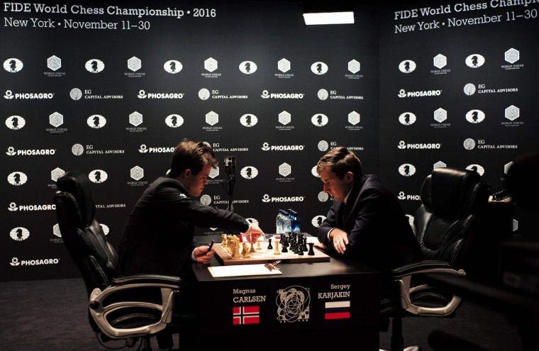 Chess grandmaster Magnus Carlsen of Norway (L) moves a piece on the board as current World chess champion and challenger Sergey Karjakin of Russia looks on during their World Chess Championship 2016 round 1 match in New York on November 11, 2016. / (AFP Photo/Jewel Samad)