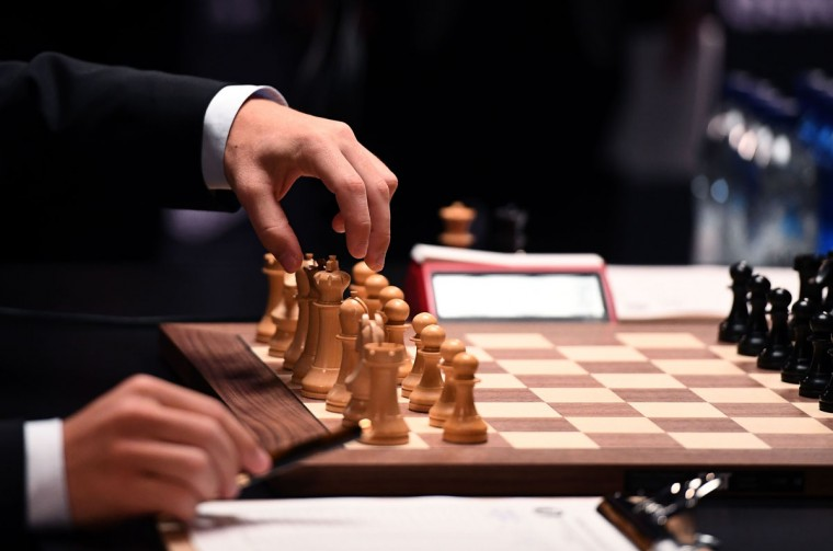 Chess grandmaster and current world chess champion Magnus Carlsen of Norway moves a piece on the board against challenger Sergey Karjakin of Russia during their World Chess Championship 2016 round 1 match in New York on November 11, 2016. / (AFP Photo/Jewel Samad)