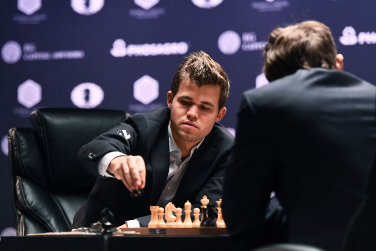 Chess grandmaster Magnus Carlsen of Norway moves a piece on the board as current World Chess Champion and challenger Sergey Karjakin of Russia (R) looks on during their World Chess Championship 2016 round 1 match in New York on November 11, 2016. / (AFP Photo/Jewel Samad)