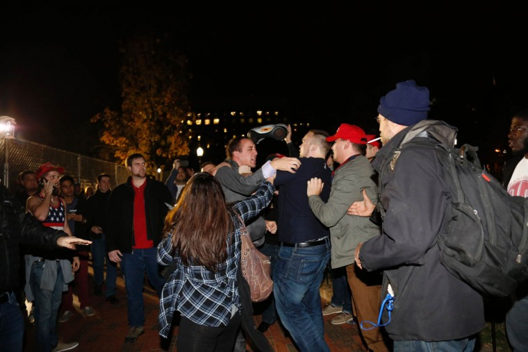 A Hillary Clinton supporter clashes with a Donald Trump supporter outside the White House early November 9, 2016 in Washington, DC. Trump stunned America and the world, riding a wave of populist resentment to defeat Hillary Clinton in the race to become the 45th president of the United States. / AFP PHOTO / Andrew Biraj