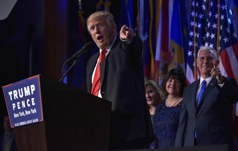 Republican presidential elect Donald Trump (L) gives a speech during election night at the New York Hilton Midtown in New York on November 9, 2016. Trump stunned America and the world Wednesday, riding a wave of populist resentment to defeat Hillary Clinton in the race to become the 45th president of the United States. / AFP PHOTO / MANDEL NGAN