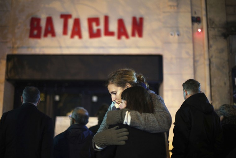 Women hug, in front of the Bataclan concert hall in Paris, Sunday, Nov. 13, 2016. France marked the anniversary of Islamic extremists' coordinated attacks on Paris with a somber silence on Sunday that was broken only by voices reciting the names of the 130 slain, and the son of the first person to die stressing the importance of integration. (AP Photo/Thibault Camus)