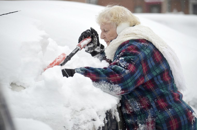 """Lorraine Amato digs out her car at Columbus Towers in Pittsfield, Mass., Monday, Nov. 21, 2016, after the region got hit with more than 10 inches of snow, according to The Berkshire Eagle. """"We knew it was snowing last night, but didn't expect this,"""" said Amato. (Ben Garver/The Berkshire Eagle via AP)"""