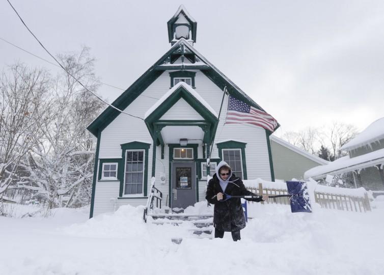 Postal clerk Pamela Bentley shovels lake-effect snow in front of the U.S. Post Office, Monday, Nov. 21, 2016, in Grafton, N.Y. (AP Photo/Mike Groll)