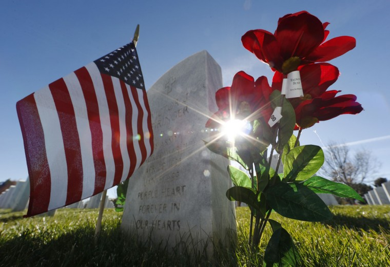 Sun glints through the artificial flowers set next to the gravestone to mark Veterans Day in Fort Logan National Cemetery on Friday, Nov. 11, 2016, in Sheridan, Colo. (AP Photo/David Zalubowski)