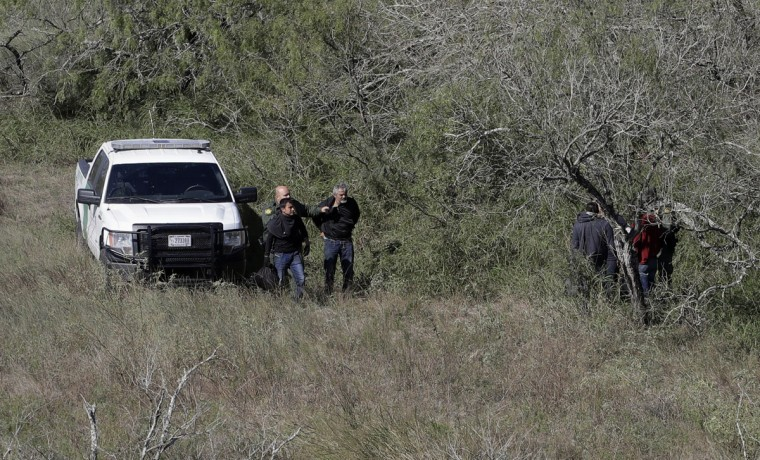 In this Tuesday, Nov. 15, 2016, photo, a U.S. Customs and Border Patrol agents stop a group of suspected illegal immigrants passing through a ranch near Edinburg, Texas. (AP Photo/Eric Gay)