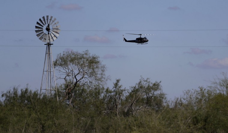 In this Tuesday, Nov. 15, 2016, photo, a U.S. Air and Marine Huey searches for immigrants who entered the county illegally on a ranch near Edinburg, Texas. (AP Photo/Eric Gay)
