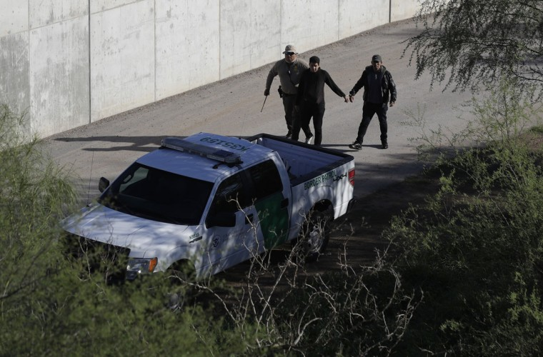 In this Wednesday, Nov. 16, 2016, photo, a U.S. Customs and Border Patrol agent walks with suspected immigrants caught entering the country illegally along the Rio Grande in Hidalgo, Texas. (AP Photo/Eric Gay)