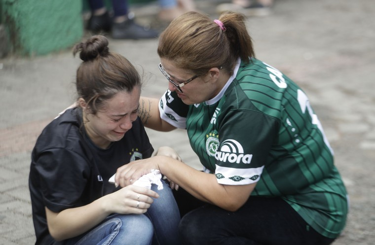 A fan of Brazil's soccer team Chapecoense consoles another outside the Arena Conda stadium in Chapeco, Brazil, Tuesday, Nov. 29, 2016. A chartered plane that was carrying the Brazilian soccer team to the biggest match of its history crashed into a Colombian hillside and broke into pieces, killing 75 people and leaving six survivors, Colombian officials said Tuesday. (AP Photo/Andre Penner)