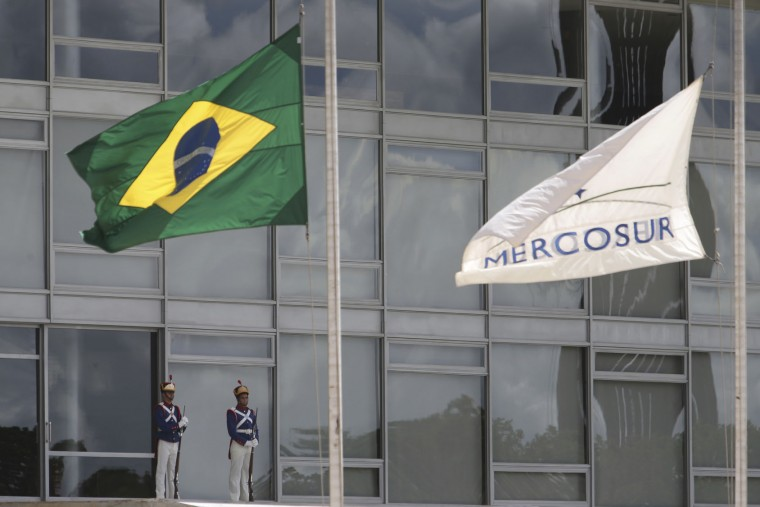 The Brazilian national flag along with a MERCOSUR banner fly at half-staff to honor plane crash victims, outside the Planalto Presidential Palace in Brasilia, Brazil, Tuesday, Nov. 29, 2016. A chartered plane carrying a Brazilian soccer team to the biggest match of its history crashed into a Colombian hillside and broke into pieces, killing 75 people and leaving six survivors, Colombian officials said Tuesday. The Brazilian government declared three days of mourning. (AP Photo/Eraldo Peres)