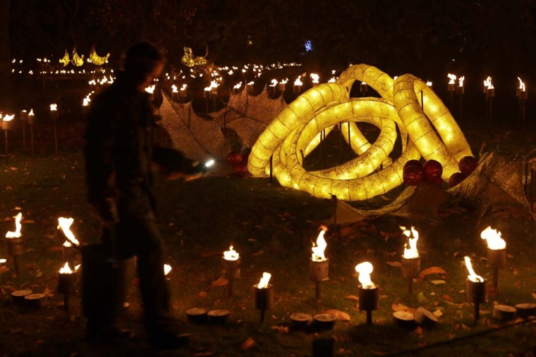 "A representative poses for photographs beside the ""Five Golden Rings"" part of the ""Fire Garden"" at the launch of ""Christmas at Kew"" at the Kew Royal Botanic Gardens in London, Tuesday, Nov. 22, 2016. The event is open to the public from November 23 until January 2 and includes an illuminated trail lit up by over 60,000 lights. (AP Photo/Matt Dunham)"