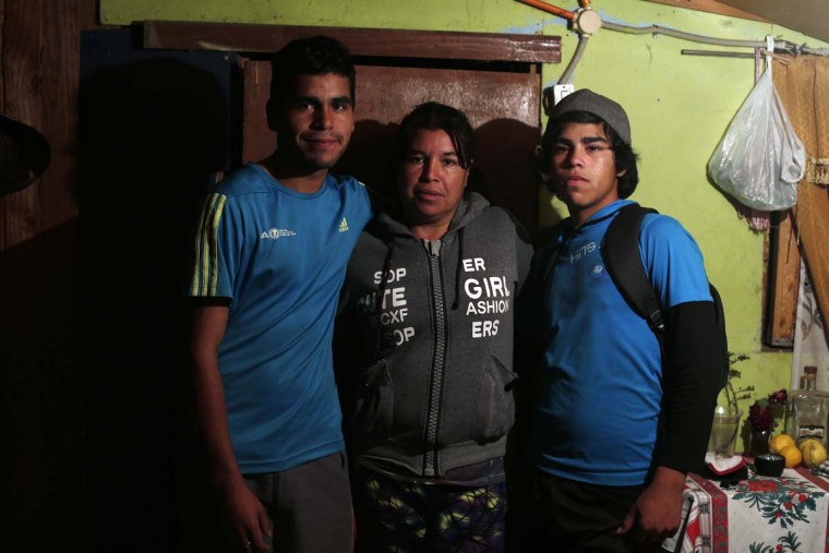 In this Oct. 19, 2016 photo, Juana Poblete, center, poses with her sons Juan Diaz Poblete, left, and Javier Diaz Poblete in Til Til, Chile. When Juana's daughter Lissette died, the goverment said that the girl had suffered from stress caused by being sexually abused. She also said the child suffered a breakdown because her family was not visiting her at the shelter. (AP Photo/Luis Hidalgo)