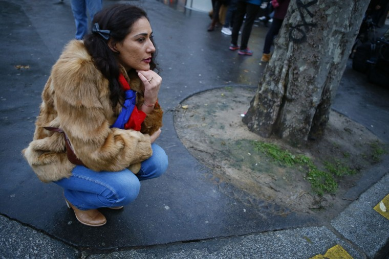 Dalila, from Paris, pays respect in front of the Bataclan concert hall in Paris, France, Sunday, Nov. 13, 2016 after a ceremony held for the victims of last year's Paris attacks which targeted the Bataclan concert hall as well as a series of bars and killed 130 people. (AP Photo/Francois Mori)
