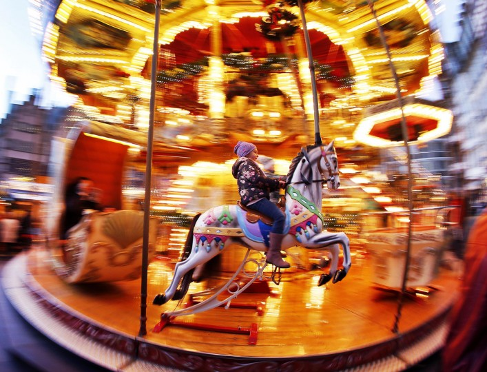 A girl rides a horse on a merry-go-round on the Christmas market in Frankfurt, Germany, Monday, Nov. 28, 2016.(AP Photo/Michael Probst)