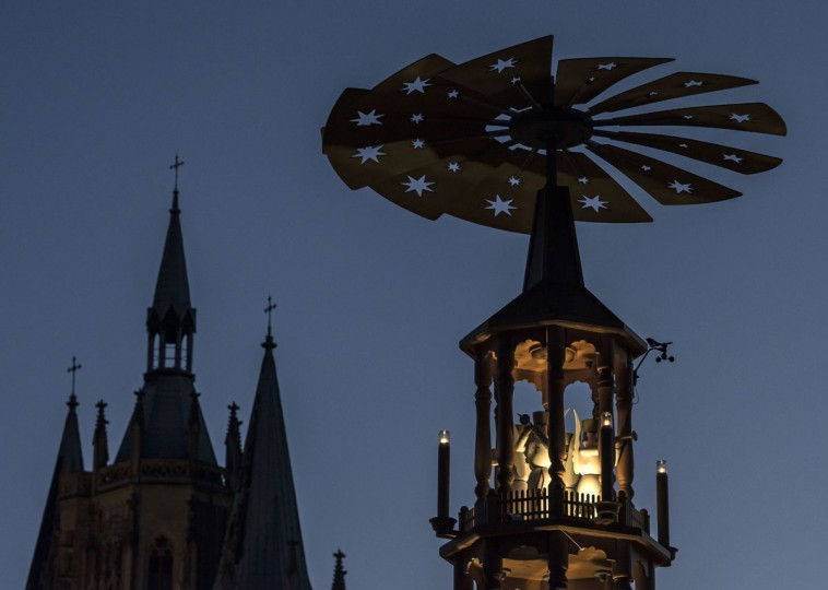 A German Christmas pyramid stands in front of the Mariendom (Cathedral of Mary) during the Christmas Fair in Erfurt, central Germany, Monday, Nov. 28, 2016. The Erfurt Christmas Market is one of the most beautiful Christmas Markets in the whole of Germany. The square is beautifully decorated with a huge, candle-lit Christmas tree and a large, hand-carved wooden creche. (AP Photo/Jens Meyer)