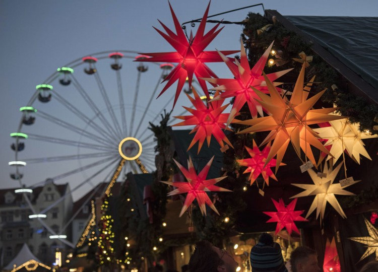 People walk in front of a stand decorated with Christmas stars during the Christmas Fair in Erfurt, central Germany, Monday, Nov. 28, 2016. The Erfurt Christmas Market is one of the most beautiful Christmas Markets in the whole of Germany. The square is beautifully decorated with a huge, candle-lit Christmas tree and a large, hand-carved wooden creche. (AP Photo/Jens Meyer)
