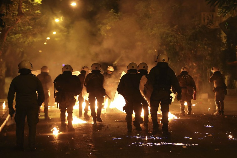 Police officers walk past flames from fire bombs thrown by demonstrators during a protest against the visit of US President Barack Obama in Athens, Tuesday, Nov. 15, 2016. Greek riot police used tear gas and stun grenades in central Athens Tuesday to disperse about 3,000 left-wing marchers protesting a visit by President Barack Obama, after they tried to enter an area declared off-limits to demonstrators. (AP Photo/Yorgos Karahalis)