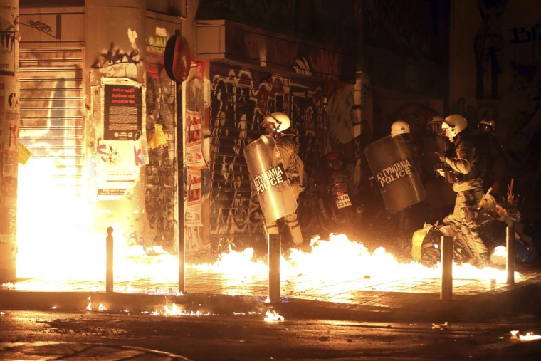 Police officers walk past flames from a fire bomb thrown by demonstrators during a protest against the visit of US President Barack Obama in Athens, Tuesday, Nov. 15, 2016. Greek riot police used tear gas and stun grenades in central Athens Tuesday to disperse about 3,000 left-wing marchers protesting a visit by President Barack Obama, after they tried to enter an area declared off-limits to demonstrators. (AP Photo/Yorgos Karahalis)