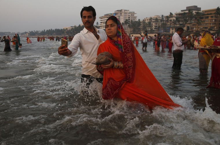 A man takes a selfie with his wife as she offers prayers to the Sun at the Arabian Sea during Chhath Puja festival in Mumbai, India, Sunday, Nov. 6, 2016. During this ancient Hindu festival, rituals are performed to thank the Sun God for sustaining life on earth. (AP Photo/Rafiq Maqbool)