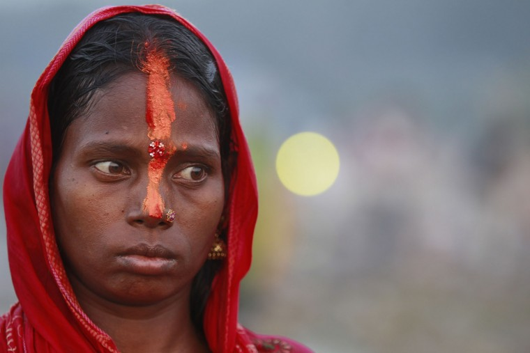 A Hindu devotee performs rituals at sunset on the banks of the Tawi River during Chhath Puja festival in Jammu, India, Sunday, Nov. 6, 2016. During Chhath, an ancient Hindu festival popular amongst the working class, rituals are performed to thank the Sun God for sustaining life on earth. (AP Photo/Channi Anand)