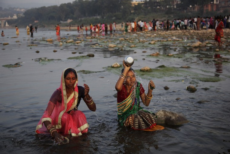 Hindu devotees perform rituals during sunset at the Tawi River during Chhath Puja festival in Jammu, India, Sunday, Nov.6, 2016. During Chhath, an ancient Hindu festival popular amongst the working class, rituals are performed to thank the Sun God for sustaining life on earth. (AP Photo/Channi Anand)