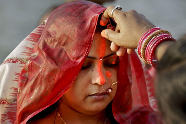 A married Hindu woman receives vermilion on her forehead as part of rituals during Chhath Puja festival on the banks of the Ganges River in Kolkata, India, Sunday, Nov. 6, 2016. During Chhath, an ancient Hindu festival, rituals are performed to thank the Sun God for sustaining life on earth. (AP Photo/Bikas Das)