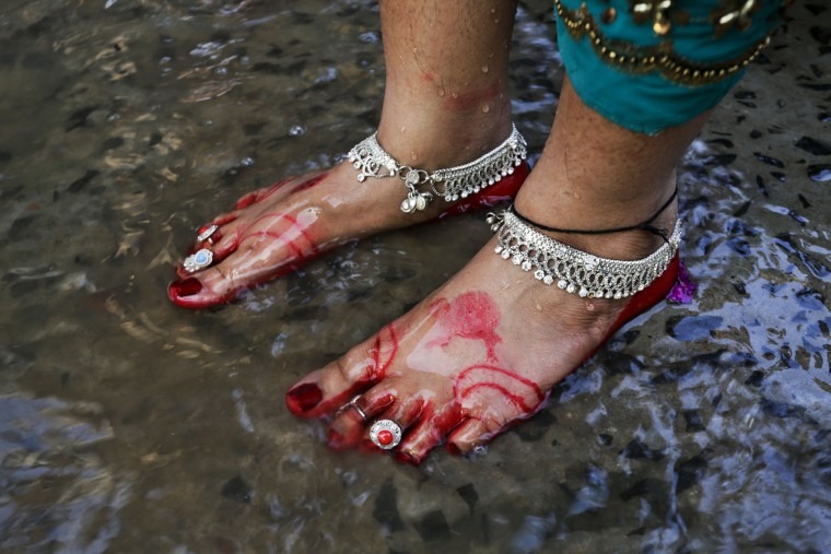A Hindu devotee who has her feet decorated stands in the Ganges River for performing rituals during Chhath Puja festival in Kolkata, India, Sunday, Nov. 6, 2016. During Chhath, an ancient Hindu festival, rituals are performed to thank the Sun God for sustaining life on earth. (AP Photo/Bikas Das)