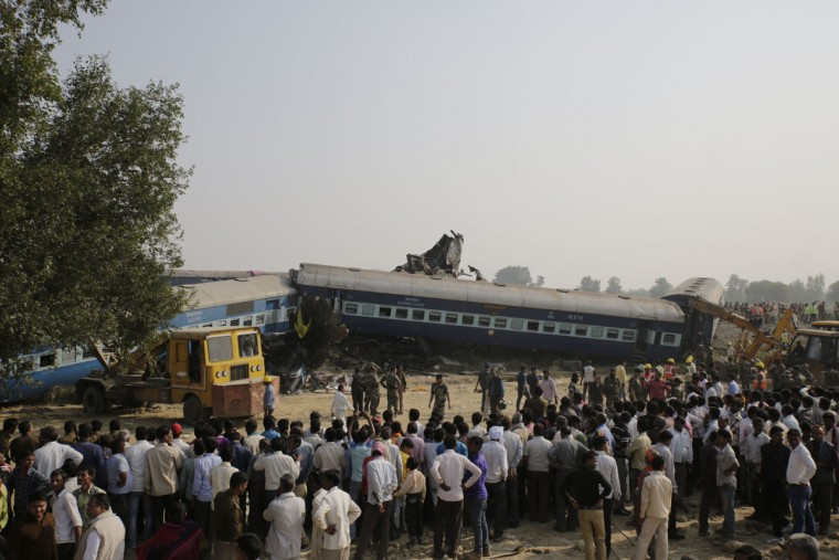 People gather after 14 coaches of an overnight passenger train rolled off the track near Pukhrayan village Kanpur Dehat district, Uttar Pradesh state, India, Sunday, Nov. 20, 2016. Dozens were killed and dozens more were injured in the accident. (AP Photo/Rajesh Kumar Singh)