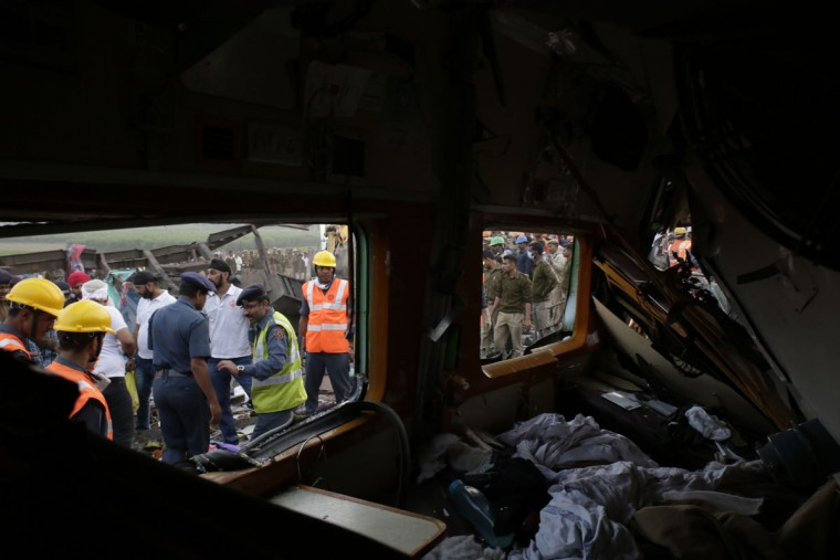 Rescuers search among debris after 14 coaches of an overnight passenger train rolled off the track near Pukhrayan village Kanpur Dehat district, Uttar Pradesh state, India, Sunday, Nov. 20, 2016. Dozens were killed and dozens more were injured in the accident. (AP Photo/Rajesh Kumar Singh)