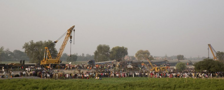 Rescuers use machinery to lift debris after 14 coaches of an overnight passenger train rolled off the track near Pukhrayan village Kanpur Dehat district, Uttar Pradesh state, India, Sunday, Nov. 20, 2016. Dozens were killed and dozens more were injured in the accident. (AP Photo/Rajesh Kumar Singh)