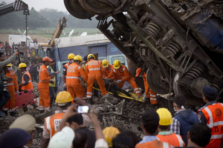 Rescuers pull out a body from the debris after 14 coaches of an overnight passenger train rolled off the track near Pukhrayan village Kanpur Dehat district, Uttar Pradesh state, India, Sunday, Nov. 20, 2016. Dozens were killed and dozens more were injured in the accident. (AP Photo/Rajesh Kumar Singh)