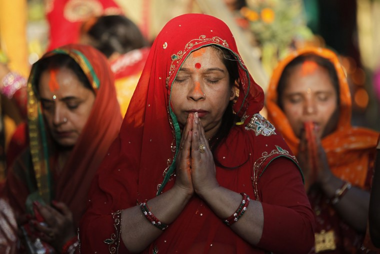 Nepalese women offer prayers to the setting Sun on the banks of the Bagmati River during the Chhath Puja festival in Kathmandu, Nepal, Sunday, Nov. 6, 2016. During Chhath, an ancient Hindu festival, rituals are performed to thank the Sun God for sustaining life on earth. (AP Photo/Niranjan Shrestha)
