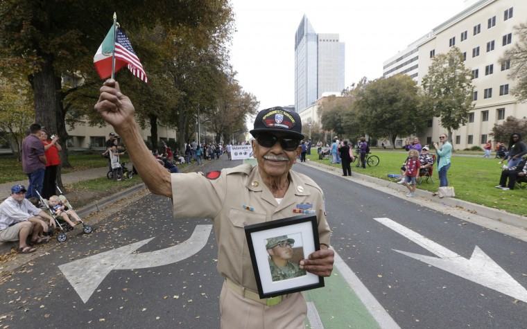 Korean War Army veteran Oscar Garcia marches down Capitol Mall during a Veterans Day parade in Sacramento, Calif., Friday, Nov. 11, 2016. Garcia displays a photo of his grandson, Daniel Garcia, 18, who graduated from Army boot camp Thursday. (AP Photo/Rich Pedroncelli)