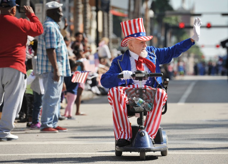 Jimmy Whitman, 90 sporting his Uncle Sam costume makes his way down Bay Street as part of the Veterans Day Parade, Friday, Nov. 10, 2016, in Jacksonville, Fla. Whitman is a veteran of both World War II and the Korean War. (Bob Self/The Florida Times-Union via AP)