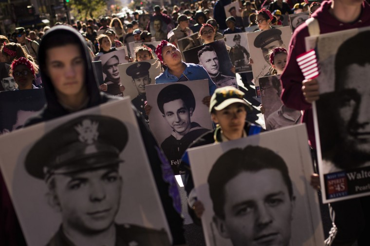 People carry photos of soldiers who died during the attack on Pearl Harbor as they march in the annual Veterans Day parade in New York, Friday, Nov. 11, 2016. (AP Photo/Andres Kudacki)