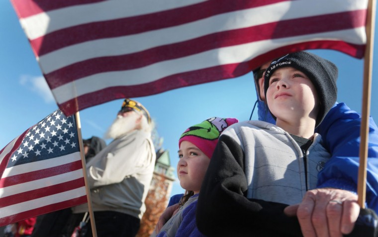 Air Force veteran Joe Manley, of Scranton, embraces his grandchildren Cailyn Manley, 6, and her brother Colin Manley, 10, both of Scranton, as they watch the Koch Conley American Legion Post 121 annual Veterans Day program on Lackawanna County Courthouse Square in Scranton, Pa., on Friday, Nov. 11, 2016. (Jake Danna Stevens/The Times & Tribune via AP)
