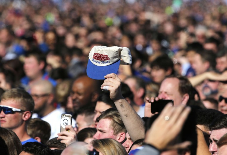 A Chicago Cubs fan holds up an opening night cap during a celebration in Grant Park honoring the World Series baseball champions Friday, Nov. 4, 2016, in Chicago. (AP Photo/Charles Rex Arbogast)