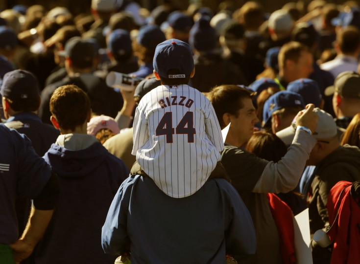 A young Chicago Cubs fan watches the celebration during a rally in Grant Park honoring the World Series baseball champions Friday, Nov. 4, 2016, in Chicago. (AP Photo/Charles Rex Arbogast)