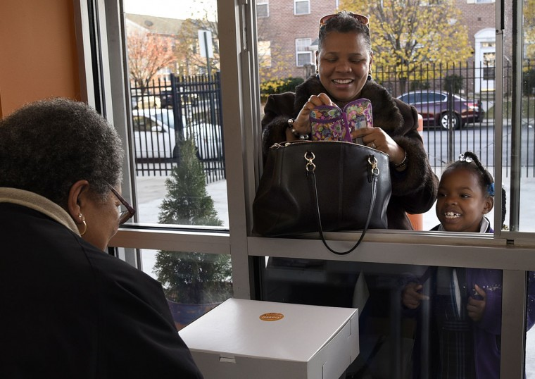 Brenda Hamlin, left, gets an order of rolls for Jules Howie, center, and her daughter Grace, 8. They are regular customers of The Avenue Bakery. (Barbara Haddock Taylor/Baltimore Sun)