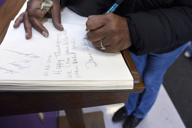 Donna Anderson of Baltimore writes a note in the guest book at The Avenue Bakery as she waits in line. (Barbara Haddock Taylor/Baltimore Sun)
