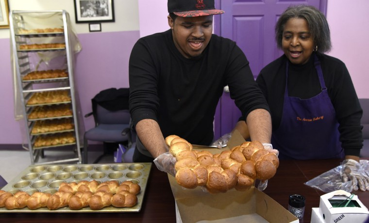 Brandon Sorrell, 19, (grandson of owner James Hamlin) and Susan Dezurn, right, family friend, place finished rolls in boxes during the Thanksgiving rush at The Avenue Bakery. (Barbara Haddock Taylor/Baltimore Sun)