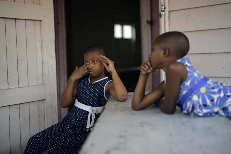 In this photo taken on Sunday, June 19, 2016, ten-year-old Safina Gatuku, left, and her sister Subiza, eight, sit in front of their room at the En Avant Les Enfants INUKA center in Goma, Democratic Republic of Congo. Abandoned by their father, they walked two days in the forest after their mother was killed by soldiers in 2009 before being pick-up by ICDC volunteers.(AP Photo/Jerome Delay)