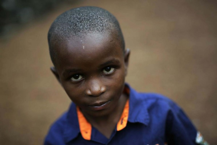 In this photo taken on Sunday, June 19, 2016, Shardrack Bahati, eight, sits outside his room at the En Avant Les Enfants INUKA center in Goma, Democratic Republic of Congo. Bahati lived on the streets of Goma when he was found by Red Cross volunteers and brought to the center in 2013. Since then, searches for his parents have been inconclusive. (AP Photo/Jerome Delay)