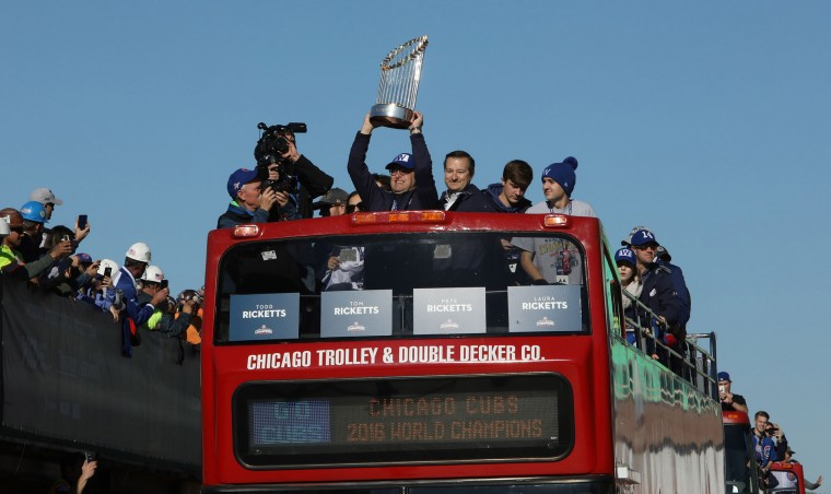 Members of the Ricketts family and the World Series trophy roll pass in a double decker bus towards the iconic Wrigley Field Chicago Cubs marquee during the parade honoring the World Series Champion Chicago Cubs, Friday, Nov. 4, 2016 in Chicago. (Antonio Perez/Chicago Tribune/TNS)