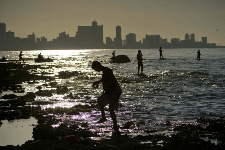 In this Nov. 11, 2016 photo, people fish on Chivo beach as the sun sets in Havana, Cuba. Much of Cuba's coastline remains free of the large-scale building that has damaged ecosystems in the rest of the Caribbean, and the island's industrial fishing fleet was devastated by the fall of the Soviet Union. (AP Photo/Ramon Espinosa)