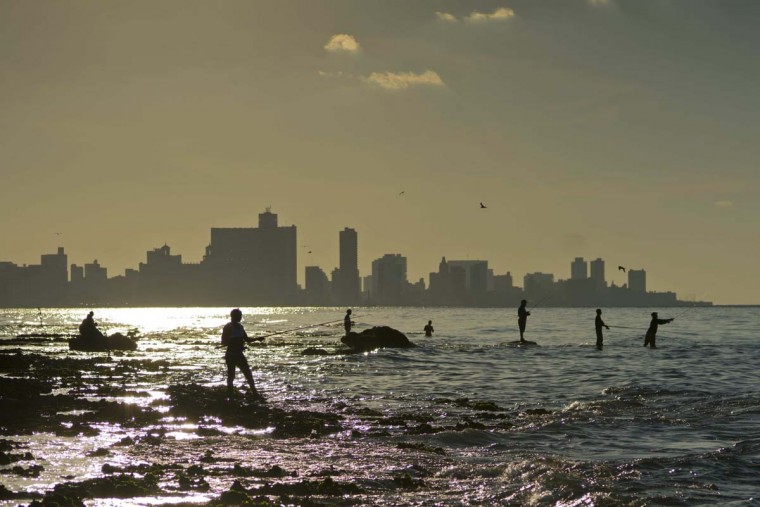 In this Nov. 11, 2016 photo, people fish off Chivo beach in Havana, Cuba. Cuba has been renowned for its fishing at least since the days of Ernest Hemingway, and foreigners by the thousands come each year to fish in waters largely protected by Cuba's lack of development. (AP Photo/Ramon Espinosa)